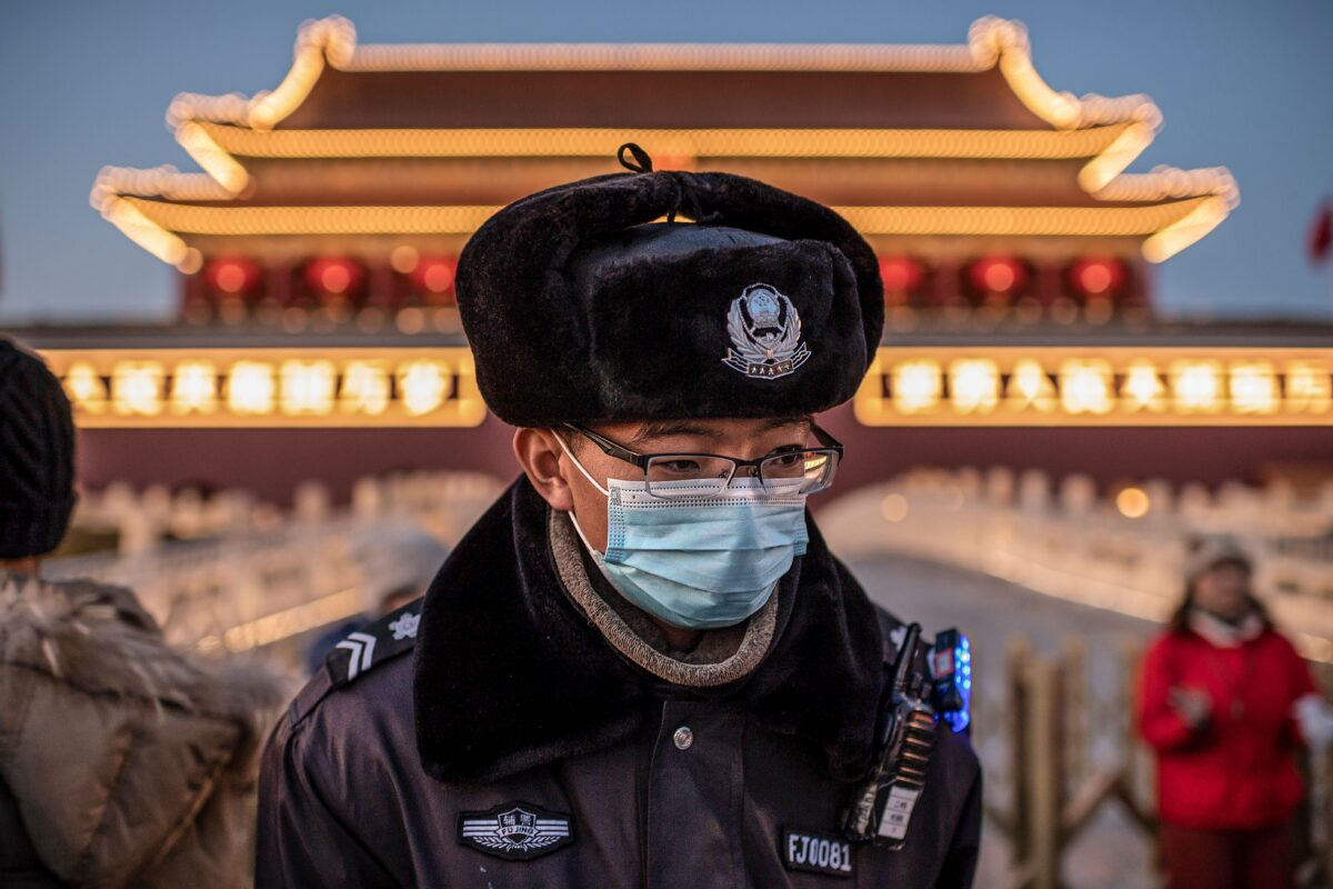 TOPSHOT - A police officer wearing a protective mask walks past the portrait of late communist leader Mao Zedong (not pictured) at Tiananmen Gate in Beijing on January 23, 2020. - Large-scale Lunar New Year events in Beijing have been cancelled as part of national efforts to control the spread of a new SARS-like virus, city authorities announced on January 23. (Photo by NICOLAS ASFOURI / AFP) (Photo by NICOLAS ASFOURI/AFP via Getty Images)